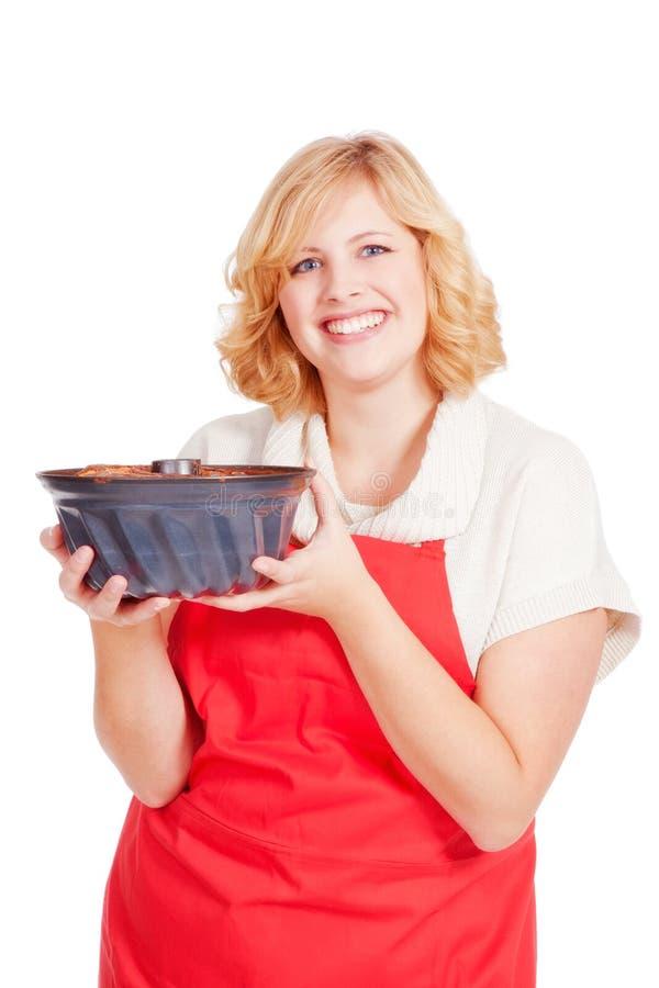 Femme blonde avec le gâteau de bundt et le tablier rouge photo libre de droits