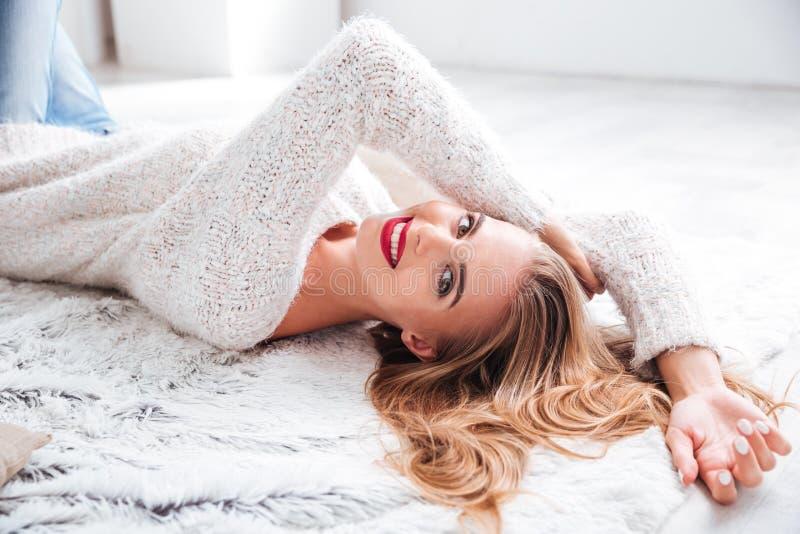 Femme blonde avec le rouge à lèvres rouge se trouvant sur le plancher à l'intérieur photos stock