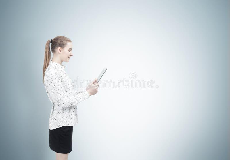 Femme blonde avec un comprimé, vue de côté photos stock