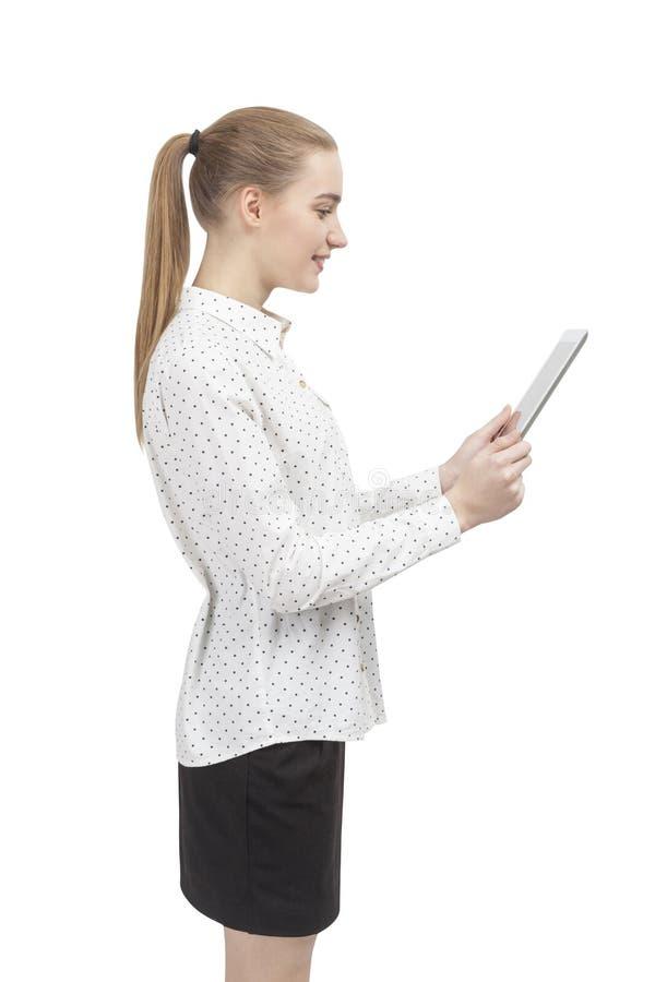 Femme blonde avec un comprimé, vue de côté d'isolement photo stock