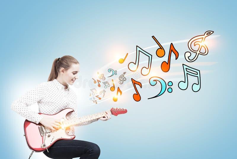 Femme blonde avec une guitare, blule de notes photo stock