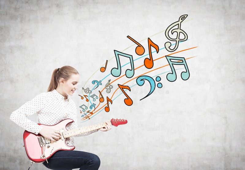 Femme blonde avec une guitare, notes images stock