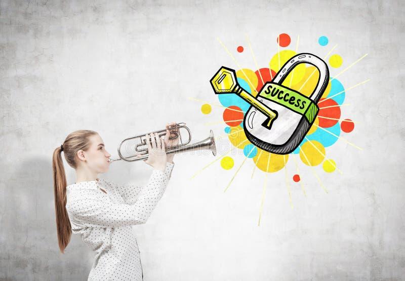 Femme blonde avec une trompette et une clé de succès photographie stock libre de droits