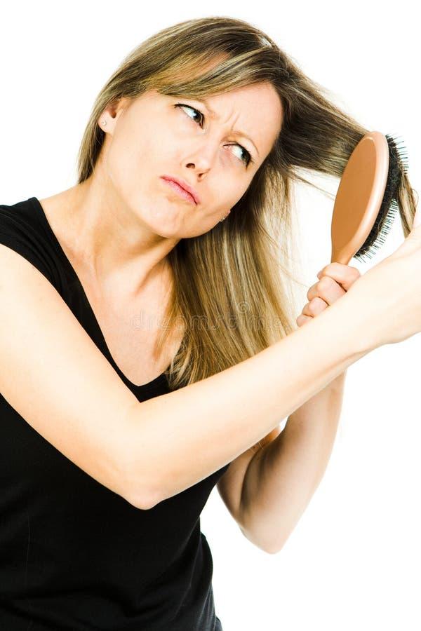 Femme blonde ayant le probl?me avec balayer de longs cheveux embrouill?s droits avec la brosse ? cheveux photo stock