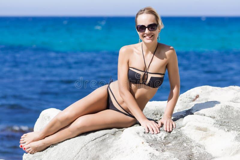Femme blonde bronzée aux cheveux courts reposant sur la roche image stock