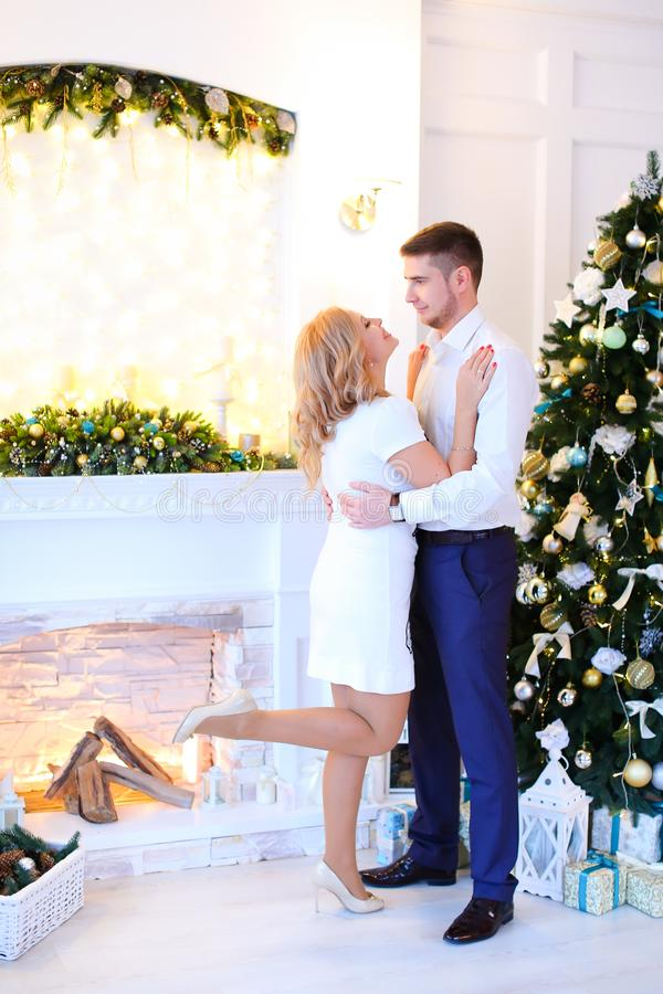 Femme blonde caucasienne étreignant le mari près de l'arbre de Noël photos libres de droits