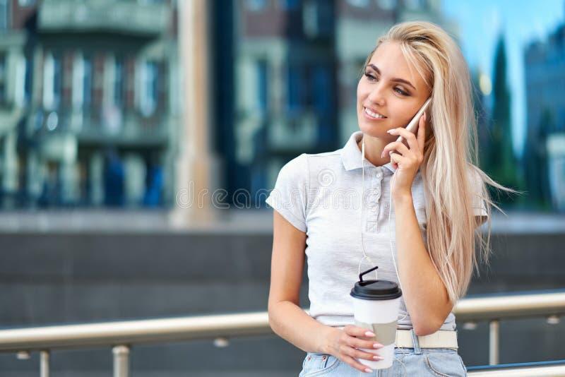 Femme blonde d'affaires parlant au téléphone portable avec le client photos libres de droits