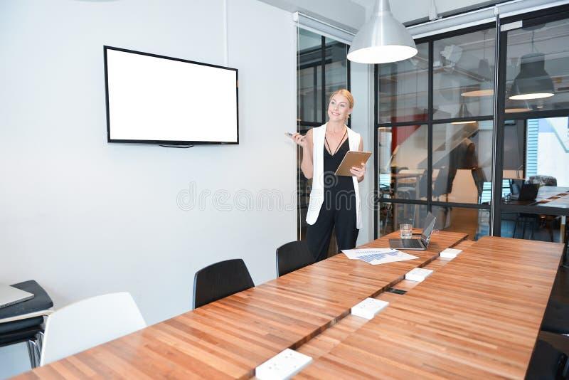 Femme blonde d'affaires présent un projet sur l'écran vide TV images libres de droits