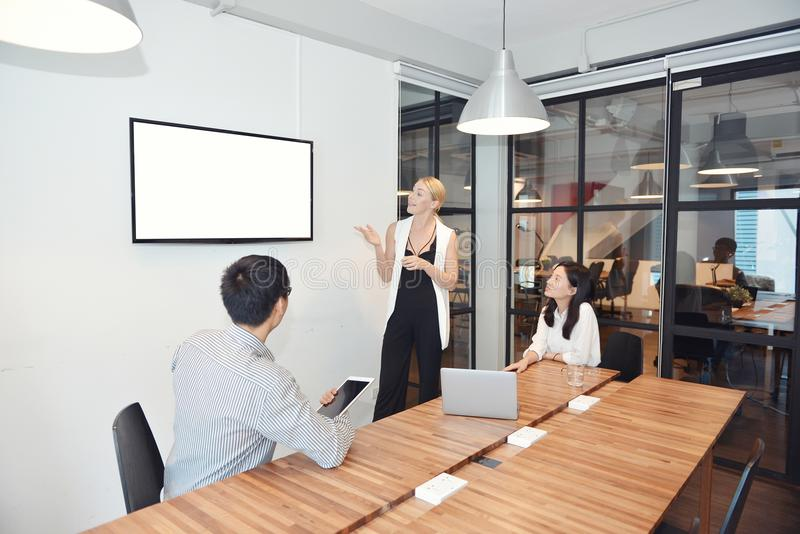 Femme blonde d'affaires présent un projet sur l'écran vide TV images stock