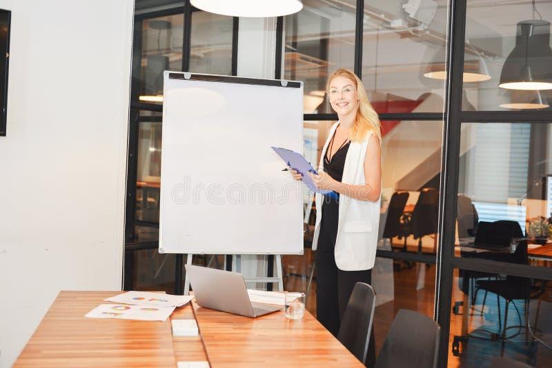 Femme blonde d'affaires présent un projet sur le tableau blanc vide image libre de droits
