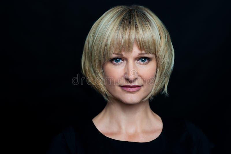 Femme blonde d'isolement sur le fond noir photos libres de droits