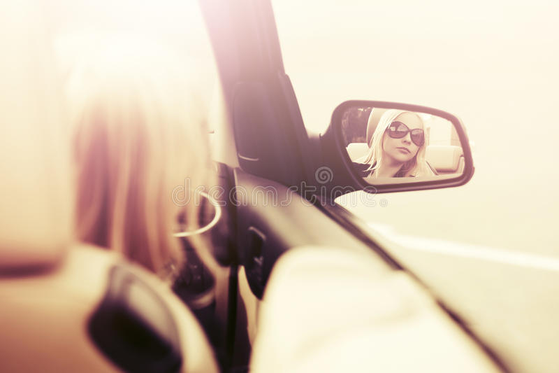 Femme blonde dans des lunettes de soleil regardant dans le miroir de vue arrière de voiture photo stock