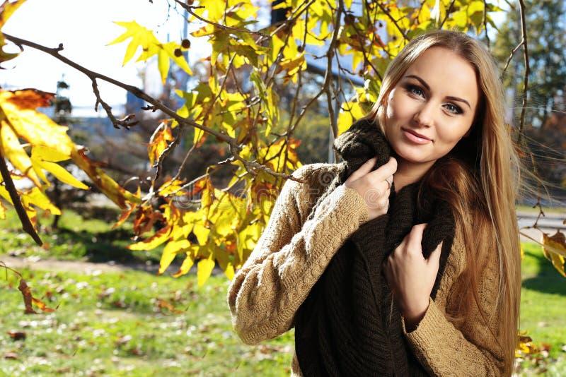 Femme blonde dans des vêtements confortables occasionnels, posant en parc d'automne photo stock