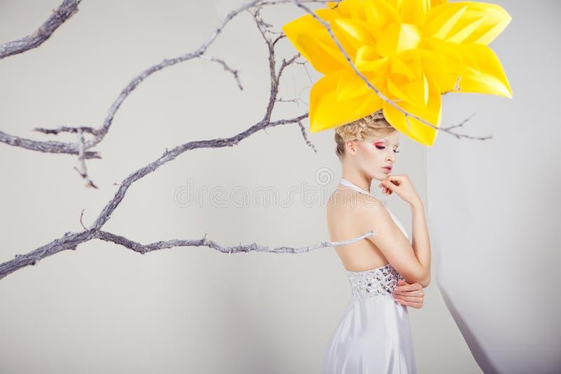 Femme blonde dans la robe blanche avec la grande fleur jaune photographie stock
