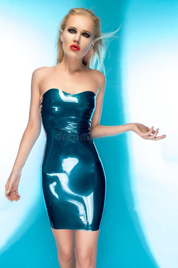 Femme blonde dans la robe bleue de latex photographie stock libre de droits