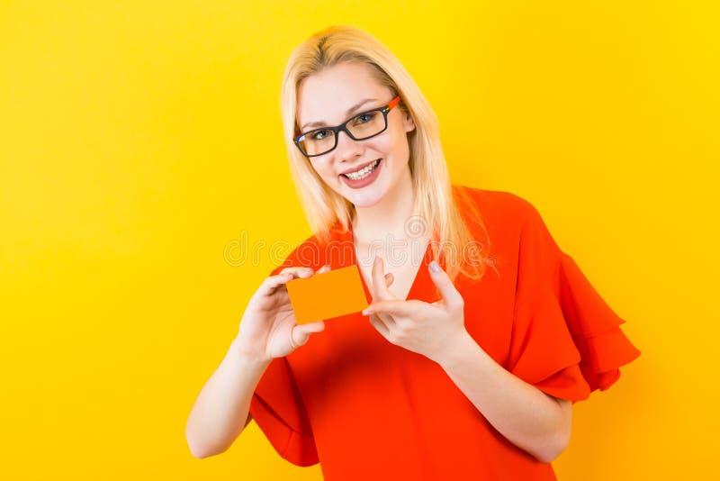 Femme blonde dans la robe rouge avec la carte de crédit images libres de droits
