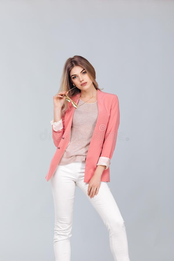 Femme blonde dans la veste occasionnelle en pastel posant dans le studio photos stock