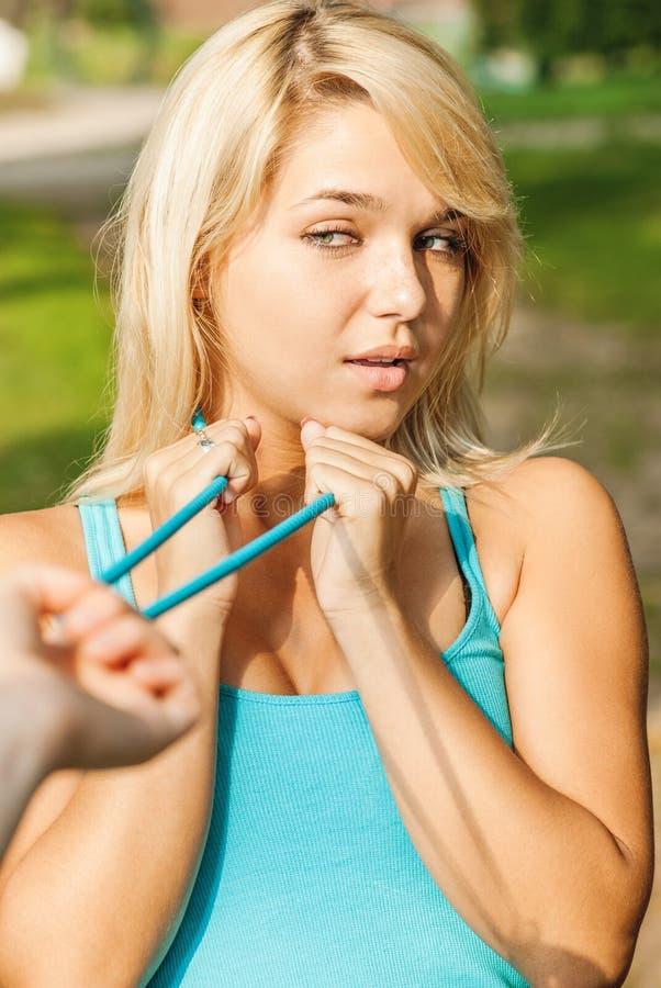 Femme blonde dans le chemisier bleu avec des perles photos stock