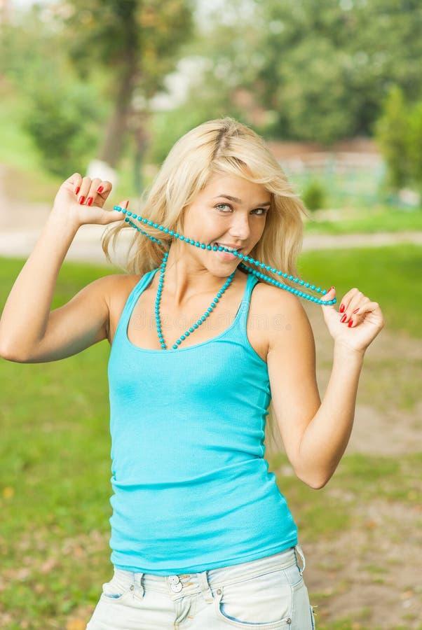 Femme blonde dans le chemisier bleu avec le sourire de perles photographie stock