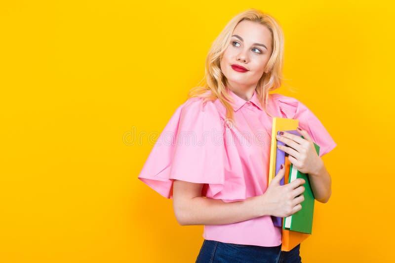 Femme blonde dans le chemisier rose avec la pile des livres images stock