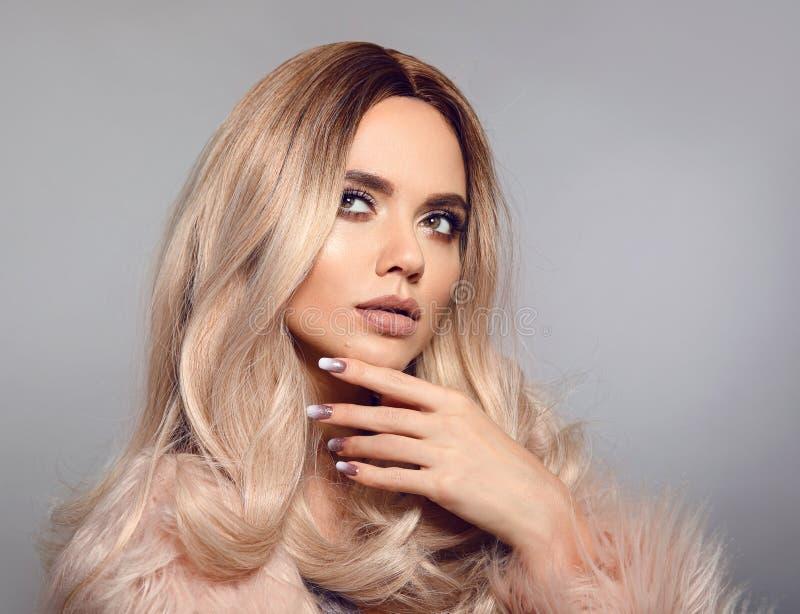 Femme blonde dans le manteau de fourrure fascinant posant dans le studio Coiffure blonde d'Ombre Portrait de fille de mode de bea photographie stock libre de droits