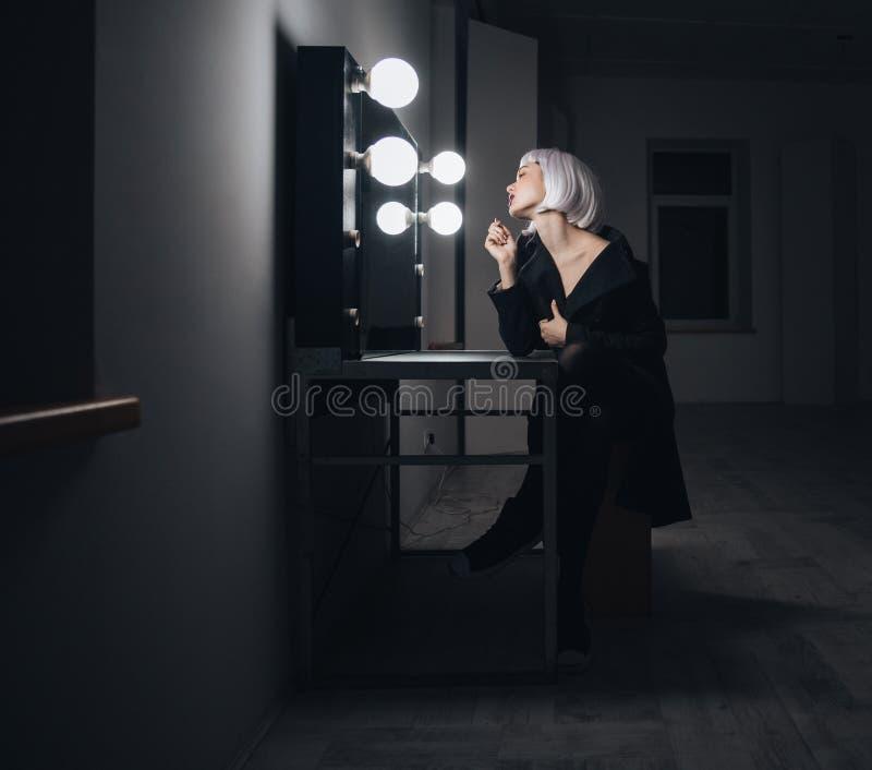 Femme blonde dans le manteau noir appliquant le rouge à lèvres dans le vestiaire photographie stock