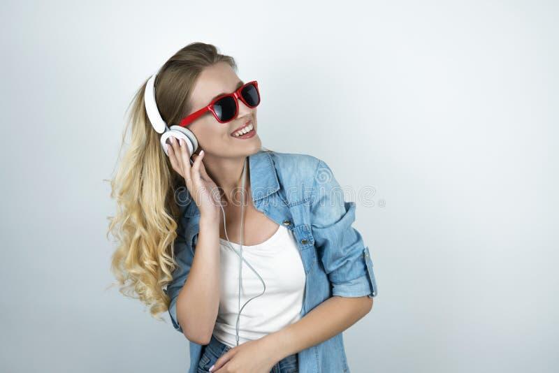 Femme blonde dans les écouteurs et des lunettes de soleil écoutant le fond blanc de sourire de musique photos stock