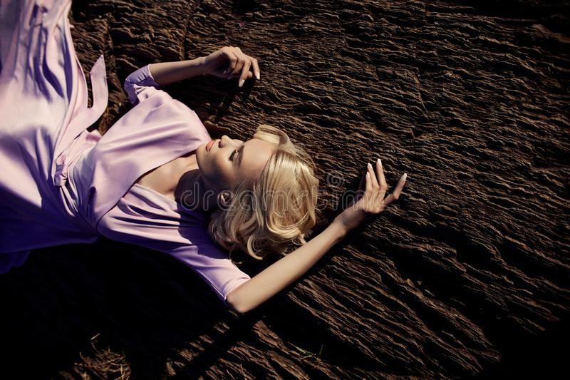 Femme blonde dans une longue robe rose se reposant sur une pierre près de la cascade Beau sourire de longs cheveux magnifiques su photos libres de droits