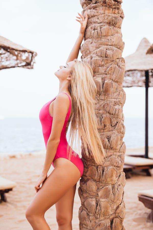 Femme blonde de beauté tenant le palmier proche sur la plage de mer de station de vacances photo stock