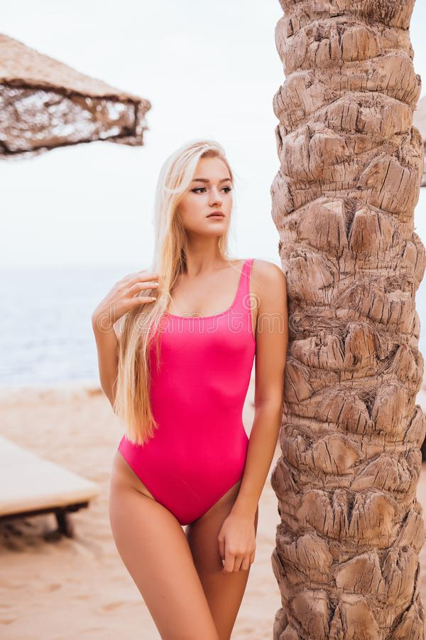 Femme blonde de beauté tenant le palmier proche sur la plage de mer de station de vacances image stock