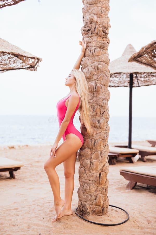 Femme blonde de beauté tenant le palmier proche sur la plage de mer de station de vacances photos stock