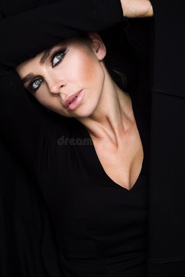 Femme blonde de beautés au sujet des yeux verts dans le chandail noir et le portrait rouge voluptueux de bouche photographie stock libre de droits