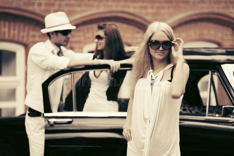 Femme blonde de jeune mode à côté de rétro voiture image libre de droits