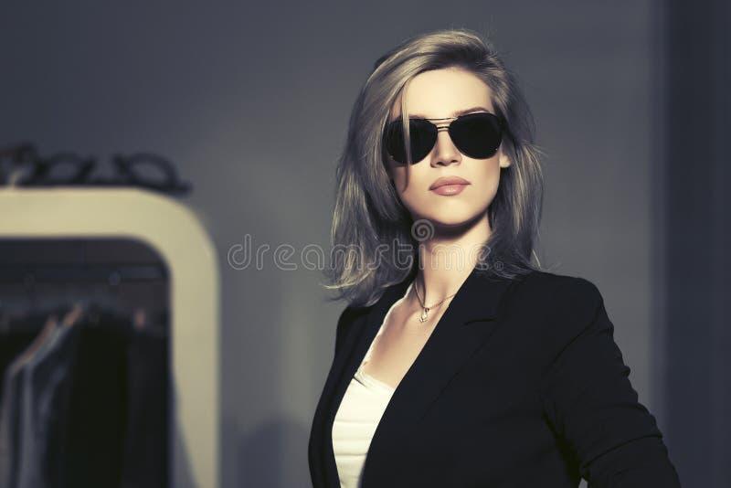 Femme blonde de jeune mode dans des lunettes de soleil dans l'intérieur de mail image stock