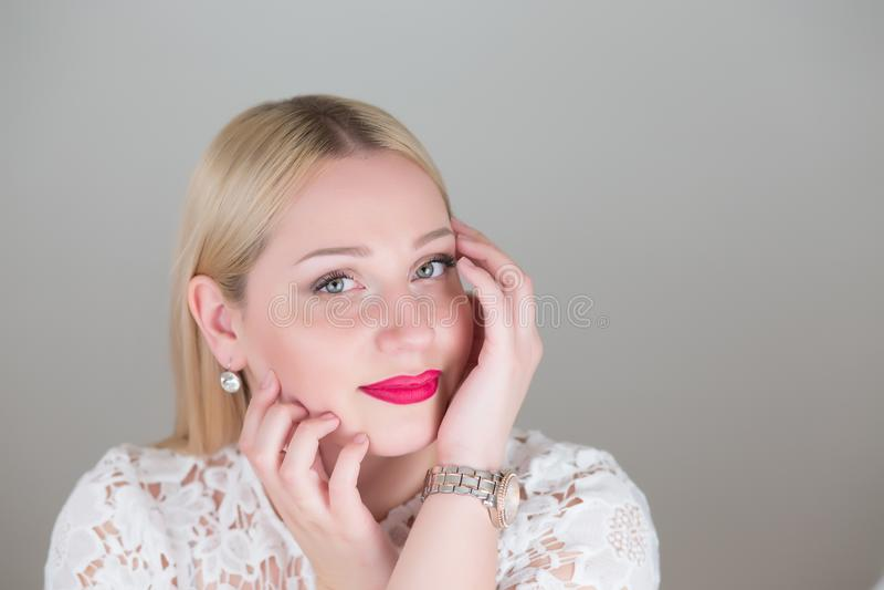 Femme blonde de portrait beau sur les backgounds gris de studio images stock