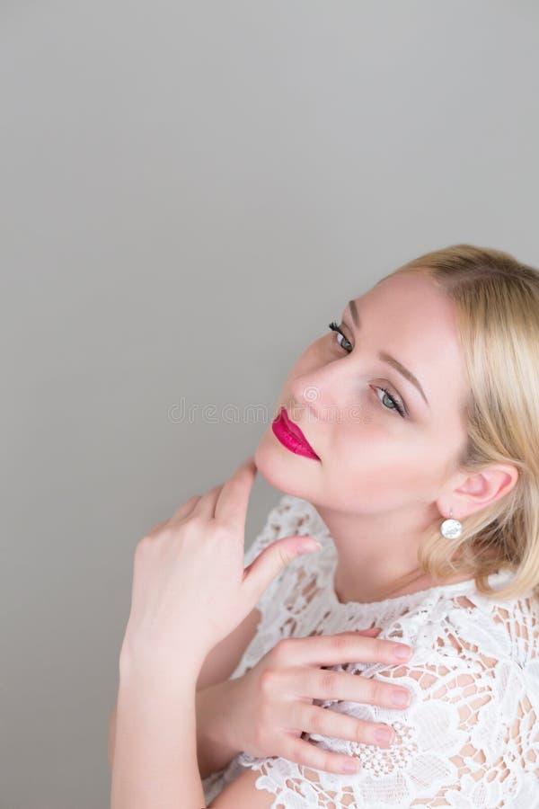 Femme blonde de portrait beau sur les backgounds gris de studio photographie stock
