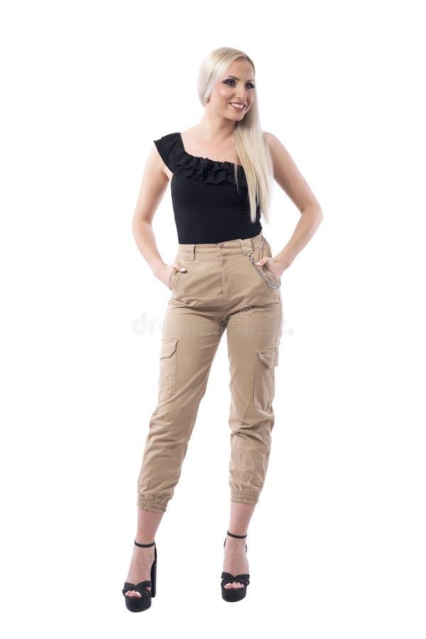 Femme blonde de rue de style de mode de luxe de regard dans des pantalons militaires souriant et regardant loin photo libre de droits