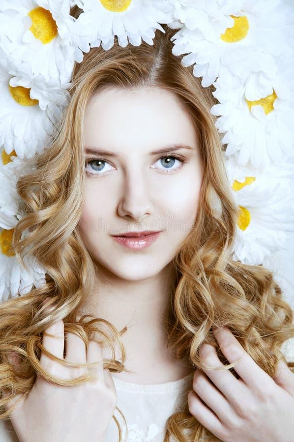 Femme blonde de sourire avec une guirlande de camomille photos libres de droits