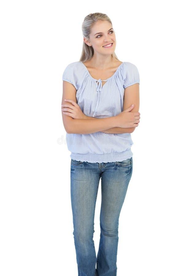 Femme blonde de sourire croisant ses bras photographie stock