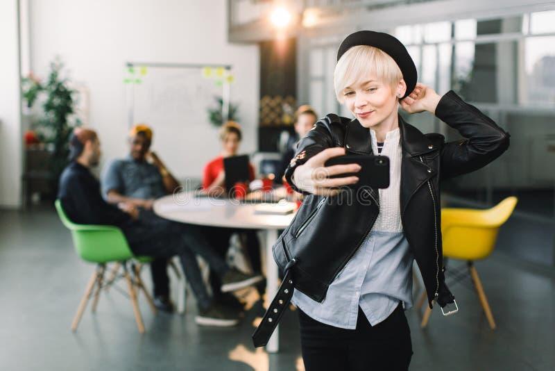 Femme blonde de sourire d'affaires dans la veste en cuir noire et le chapeau faisant le selfie au téléphone au petit bureau, jeun photographie stock