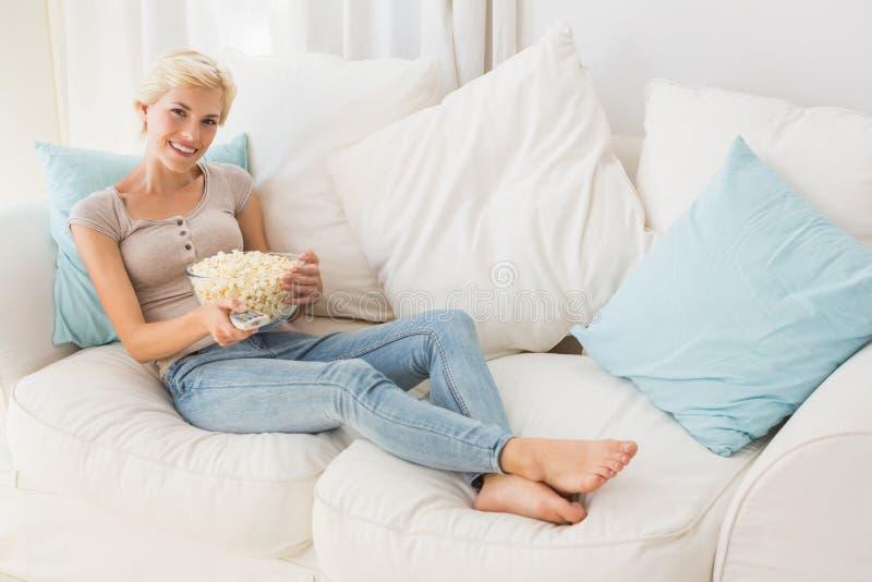 Femme blonde de sourire de portrait regardant la TV et mangeant du maïs de bruit image libre de droits