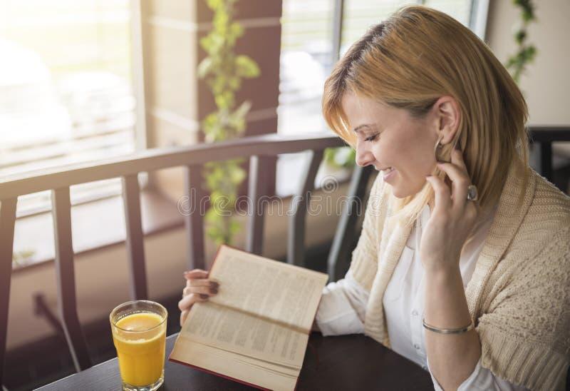 Femme blonde de sourire de jeunes dans un restaurant lisant un livre et un Dr. image stock