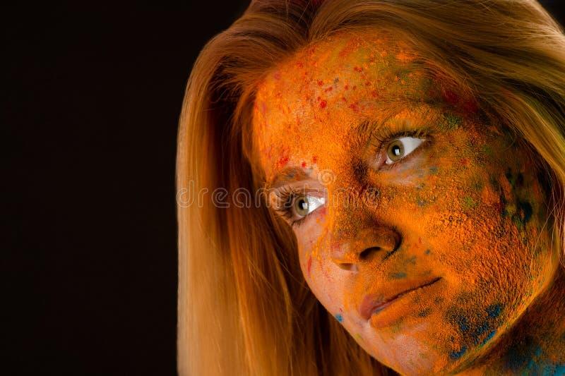 Femme blonde de visage de portrait dans des couleurs rouges Holi photo libre de droits
