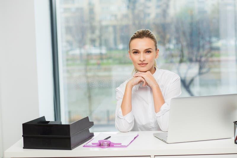 Femme blonde derrière son bureau photos stock