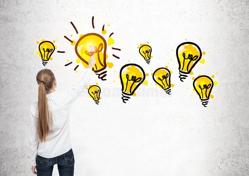 Femme blonde dessinant les ampoules images libres de droits