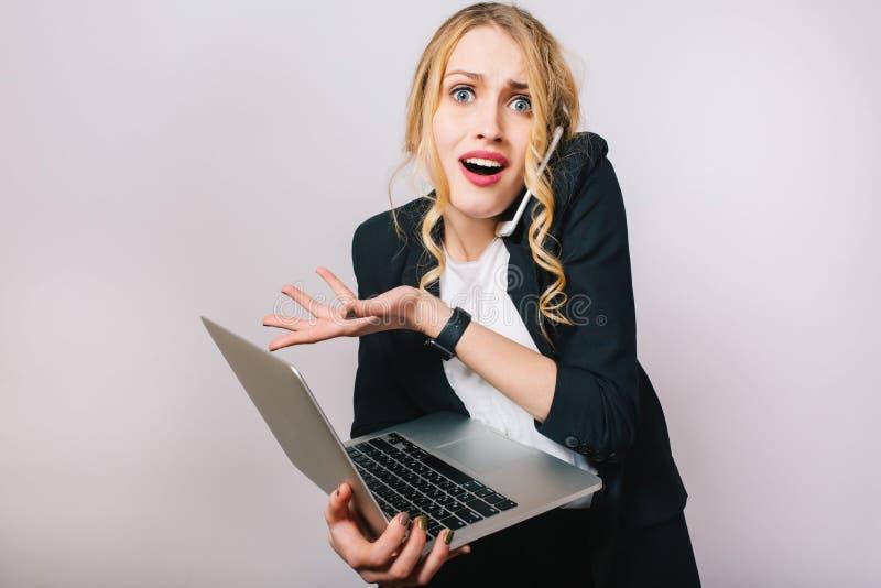 Femme blonde drôle moderne de bureau de portrait dans la chemise blanche et la veste noire sur le fond blanc Fonctionner avec l'o photo stock