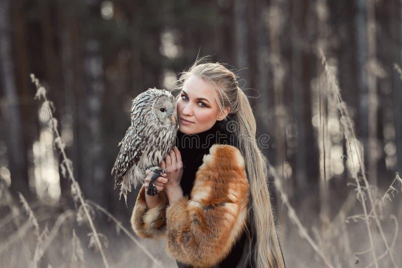 Femme blonde en automne dans le manteau de fourrure avec la première neige de hibou en main B photographie stock