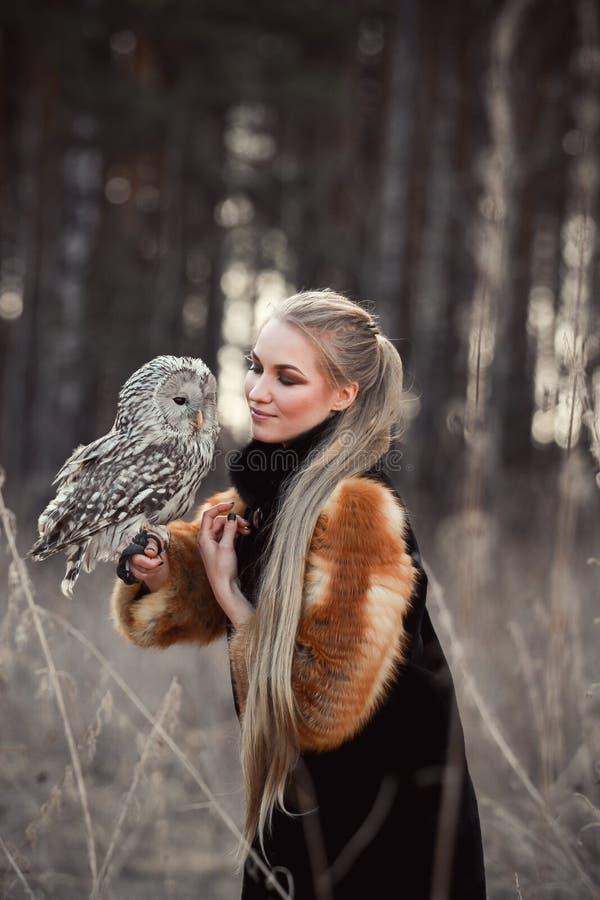 Femme blonde en automne dans le manteau de fourrure avec la première neige de hibou en main B photographie stock libre de droits