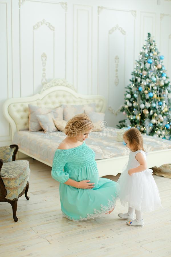 Femme blonde enceinte portant la robe bleue étreignant le ventre et se reposant avec la petite fille près de l'arbre de Noël dans images stock