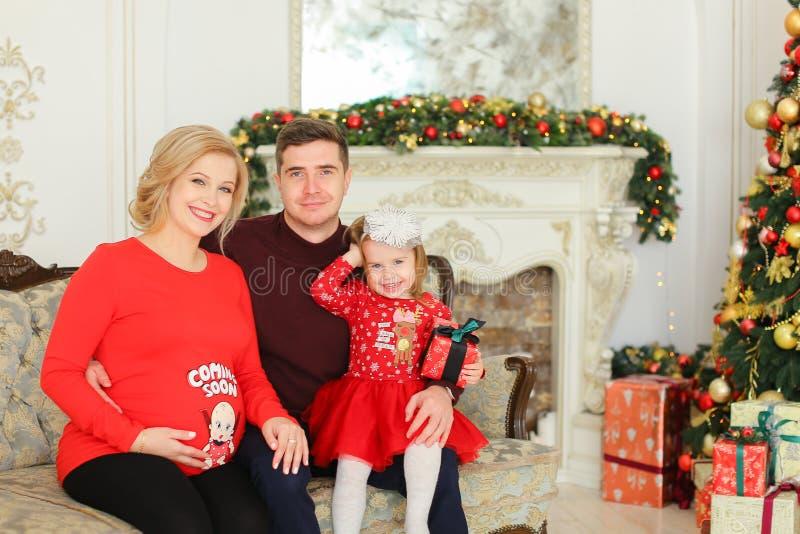 Femme blonde enceinte s'asseyant avec l'homme et la fille près de l'arbre de Noël et de la cheminée décorée image libre de droits